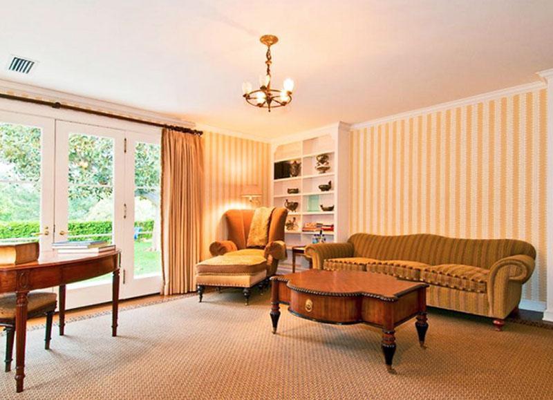 Освещают кабинет старинная люстра из обода с лампочками-свечками и изящное бра с тканевым плафоном