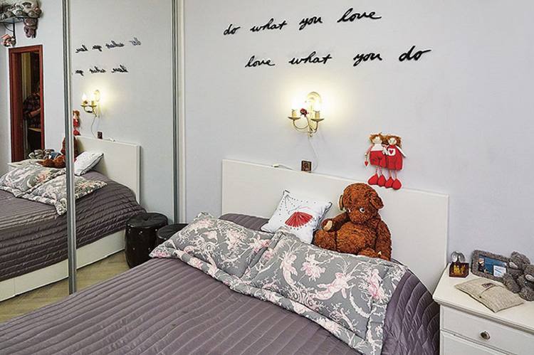Смягчает холодность интерьера изящный настенный светильник над изголовьем кровати