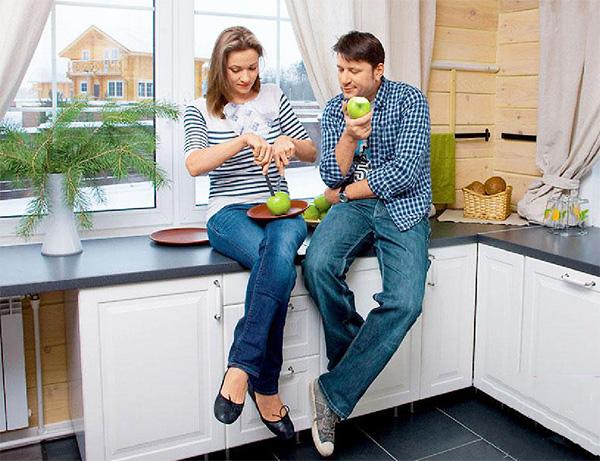 Окна на кухне украшают небольшие занавески из хлопчатобумажной ткани