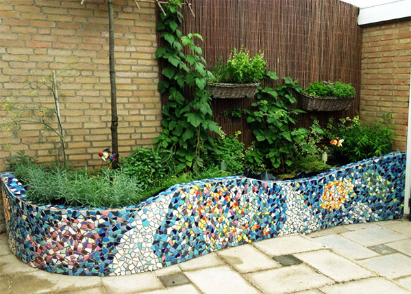 Невысокие стенки клумбы или грядки можно облицевать мозаикой из битой плитки
