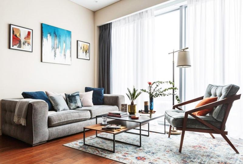 Панорамные окна в гостиной украсили белоснежным тюлем и однотонными портьерами в серой гамме