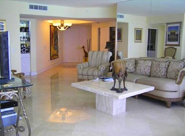 Зеркальное панно на стене визуально увеличивает просторную гостиную