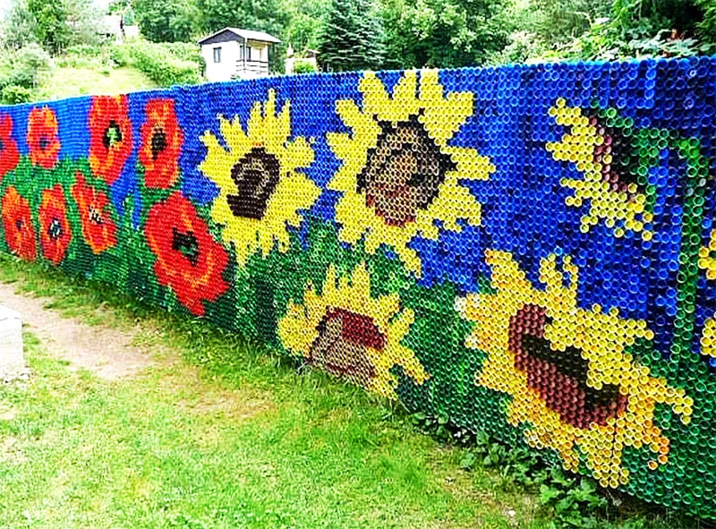 Украсить обычный сетчатый забор можно с помощью ярких крышек
