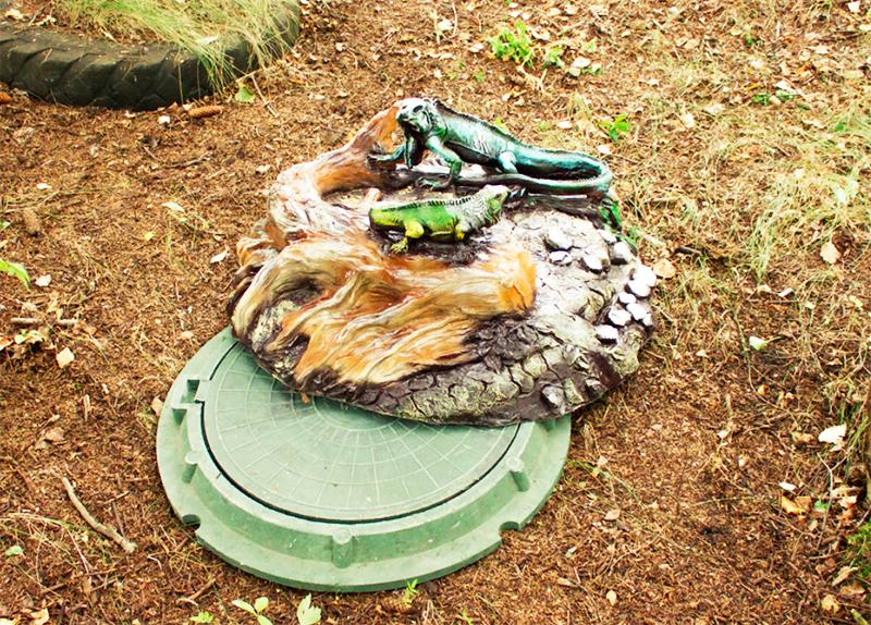 А ещё можно на крышке люка оставить декоративный элемент – что-то вроде колодца или садовой скульптуры