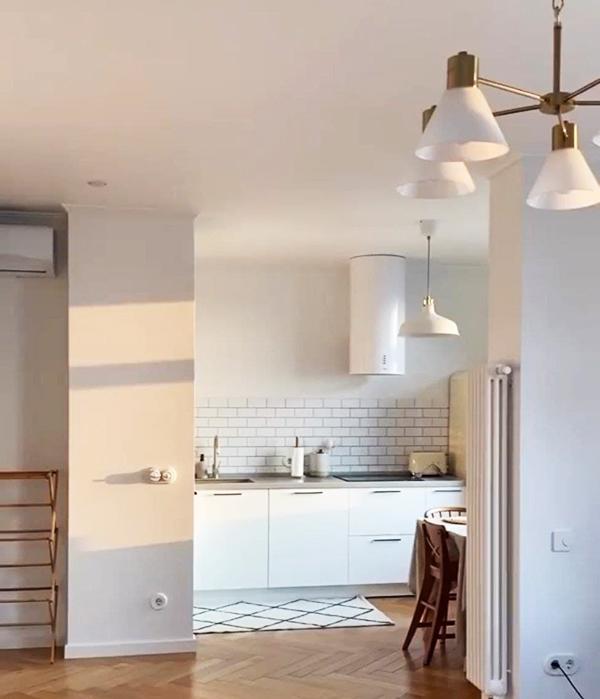 Особое внимание уделено деталям интерьера, разбавляющим белый цвет. На кухне в качестве акцентов выбран чёрно-белый ковёр и деревянные стулья в обеденной зоне