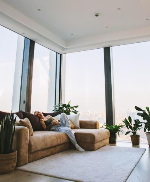 В углу гостиной, рядом с панорамными окнами, поставили красивый классический диван бежевого цвета, который хорошо гармонирует с окружающей обстановкой