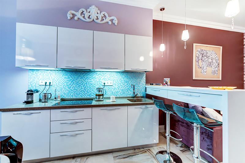 Стену над кухонными модулями украшает крупный вензельный узор из гипса