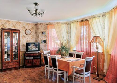 В интерьере четко прослеживается сочетание нескольких стилей: кантри, прованс, бохо и деревенский. В гостиной умело сочетаются разные детали – цветочные обои, лёгкие занавески из органзы и массивные чёрно-белые стулья